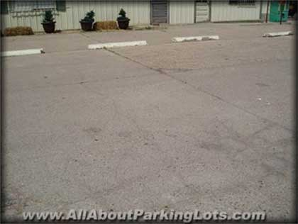 an older concrete parking lot and the effects of aging, traffic and oxidization from the sun