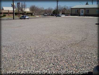 an older asphalt parking lot and the effects of aging and oxidization from the sun