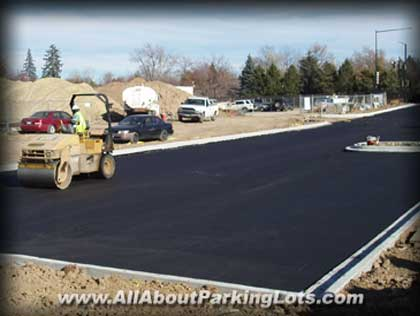 an asphalt paving contractor rolling newly laid asphalt on a parking lot
